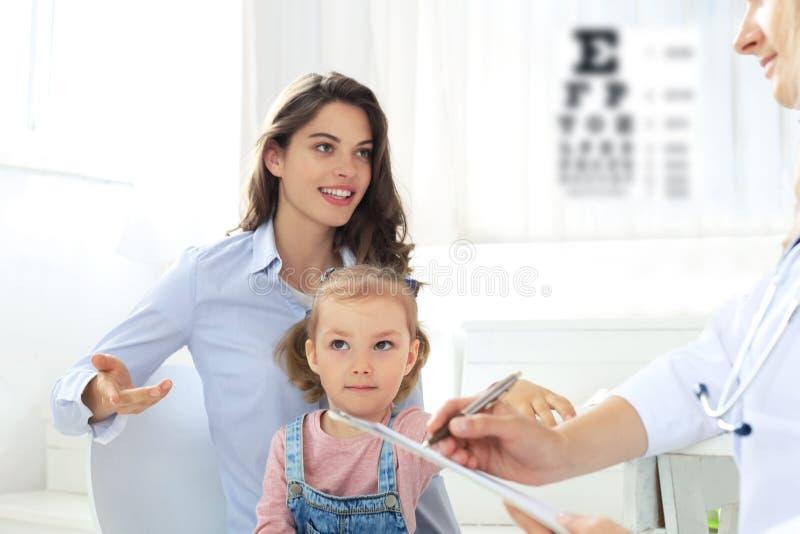 Мать и ребенок в офисе доктора встречая педиатр, они сидят на столе в больнице стоковое фото
