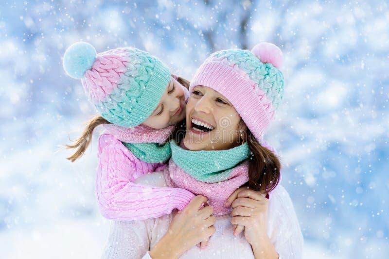 Мать и ребенок в связанных шляпах зимы в снеге стоковые фото