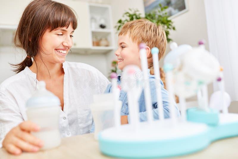 Мать и ребенок заполняют детское питание в контейнеры стоковое изображение