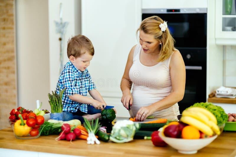 Мать и ребенок подготавливая обед стоковое фото