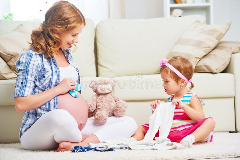 Мать и ребенок счастливой семьи беременная подготавливая одежду для ne стоковые изображения