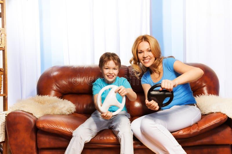 Мать и ребенок управляя с рулевыми колесами стоковое фото rf