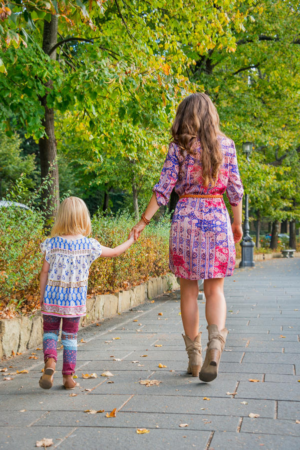 Мать и ребёнок идя в парк города стоковые фотографии rf