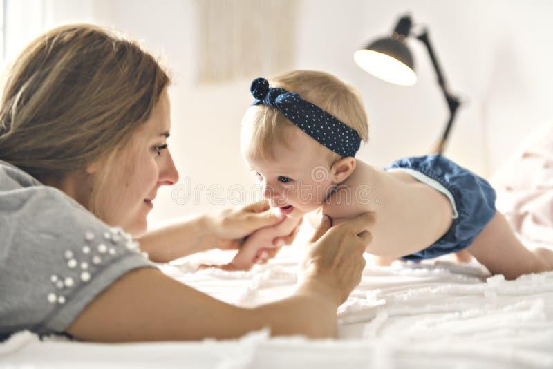 Мать и ребёнок на белой кровати стоковое изображение