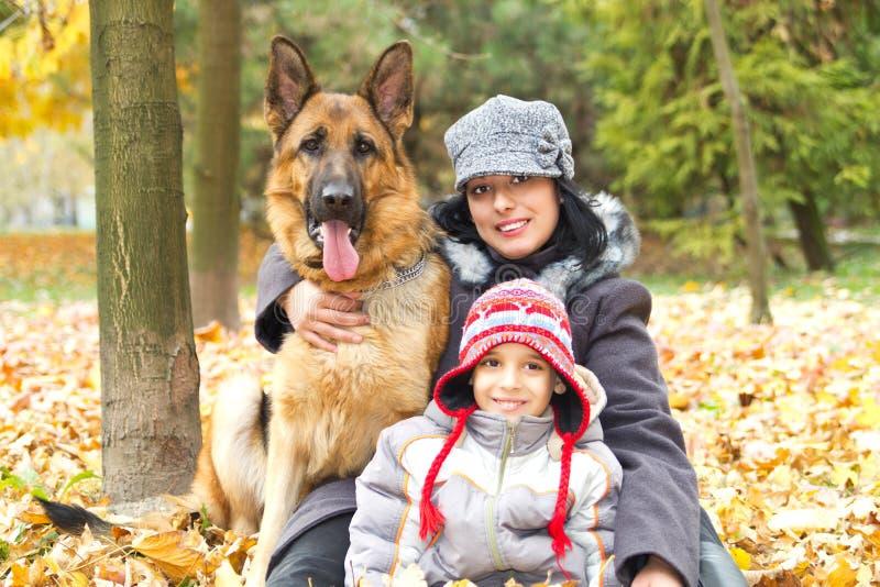 Мать и сынок с собакой в парке стоковые изображения