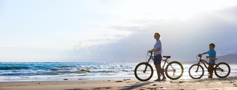 Мать и сын велосипед на пляже стоковые фото