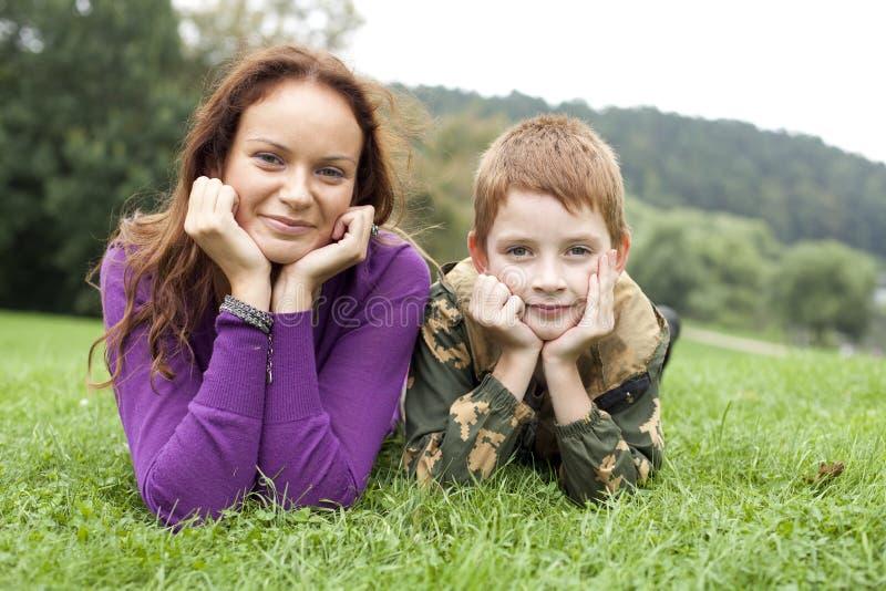 Мать и сын лежа на зеленой траве стоковые изображения