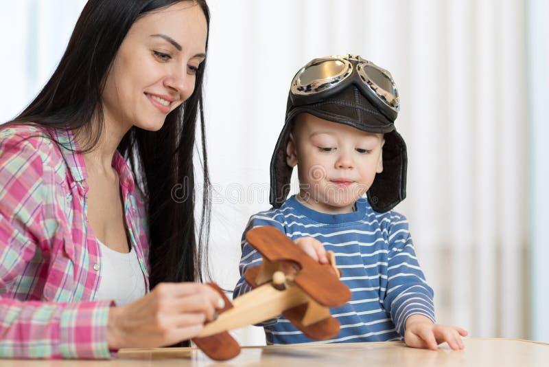 Мать и сын играют с деревянным самолетом стоковое изображение rf