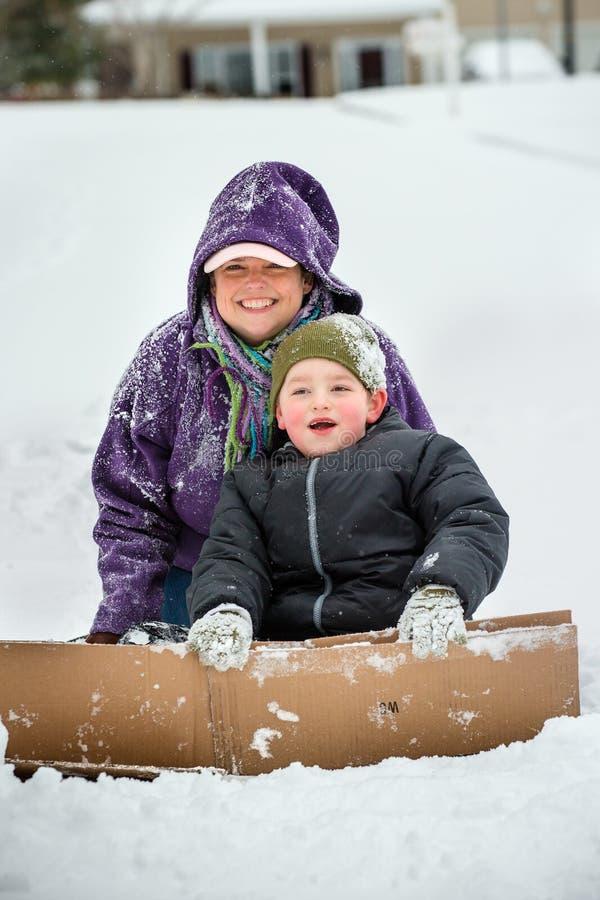 Мать и сын играя в снеге используя картон для того чтобы сползти вниз холм стоковые фото
