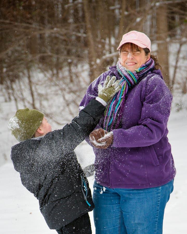 Мать и сын играя в снеге стоковое фото rf