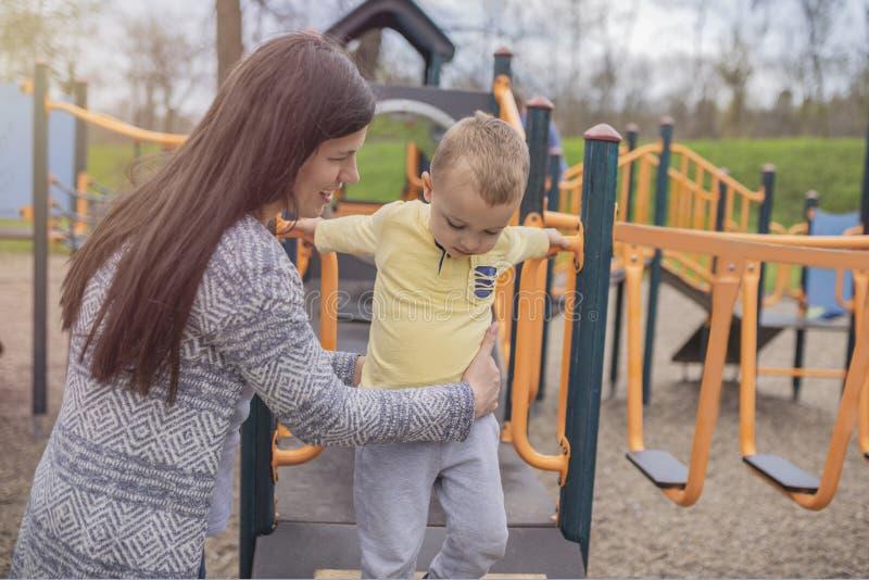 Мать и сын играя на спортивной площадке и имея потеху стоковое изображение