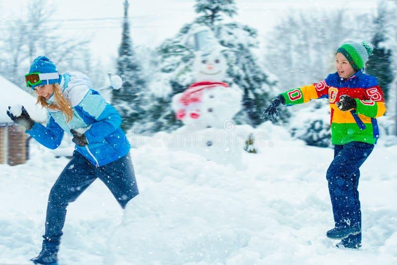 Мать и сын играя снежные комья на морозный зимний день зима снежка положения праздников мальчика Потеха зимы семьи на каникулы ро стоковые фото