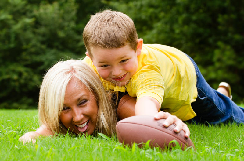 Мать и сын играя футбол outdoors стоковое изображение