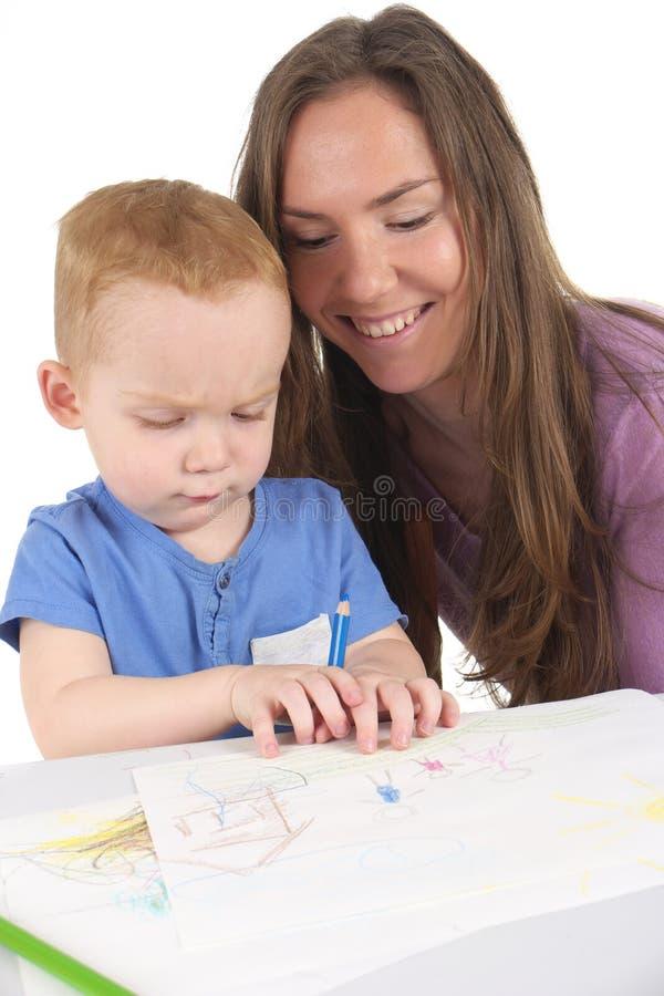 Мать и сын рисуют изображение совместно стоковые фото