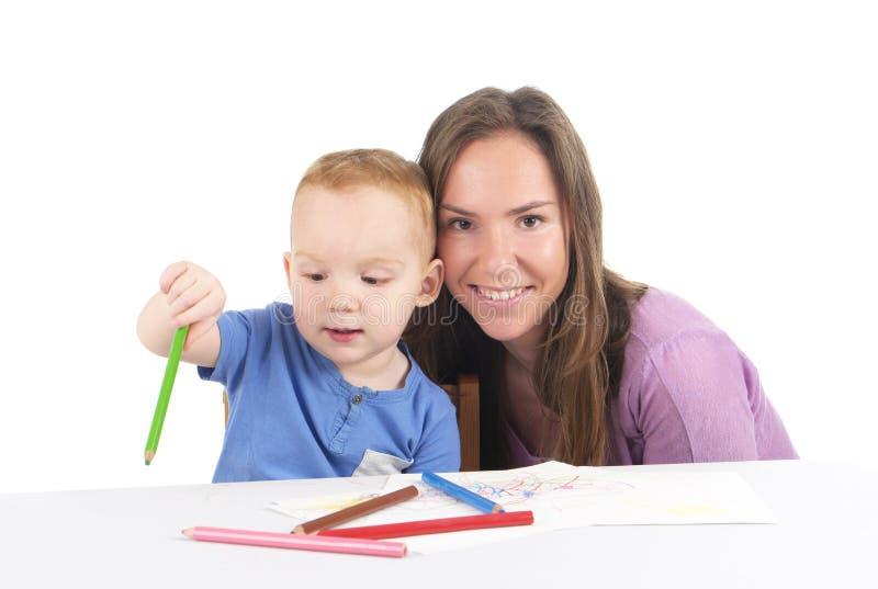 Мать и сын рисуют изображение совместно стоковые изображения