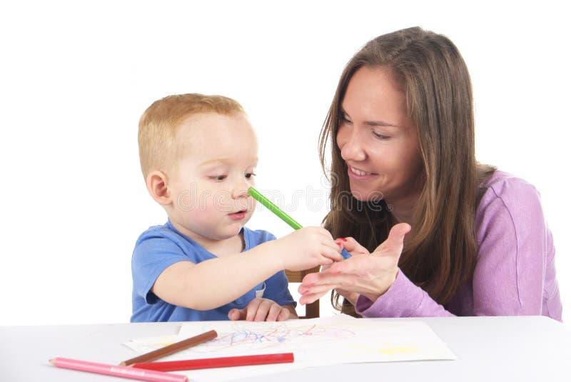 Мать и сын рисуют изображение совместно стоковое изображение