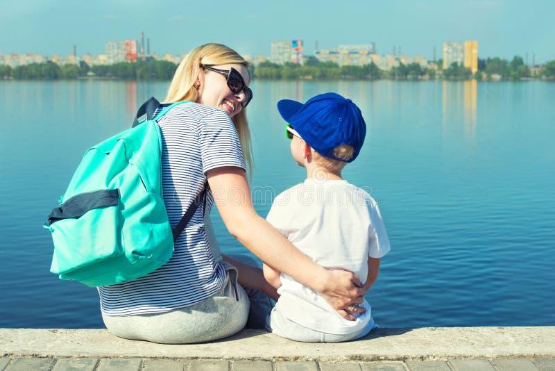 Мать и сын сидя на прогулке и взгляде на реке стоковое фото