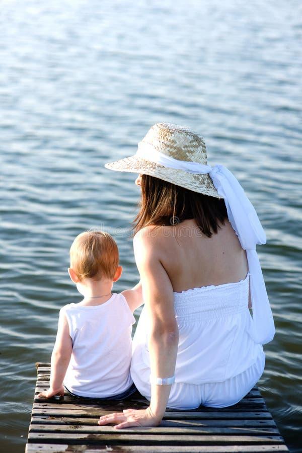 Мать и сын сидя на деревянной моле стоковое фото