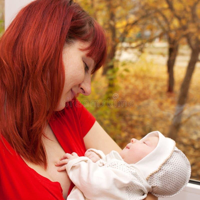 Мать и newborn младенец смотря и усмехаясь. стоковое фото rf