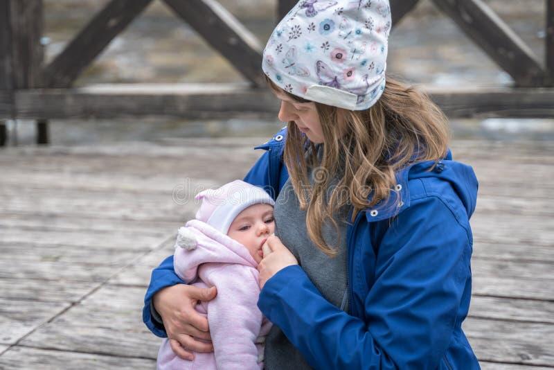Мать кормя ее newborn ребенка грудью в парке стоковые изображения rf