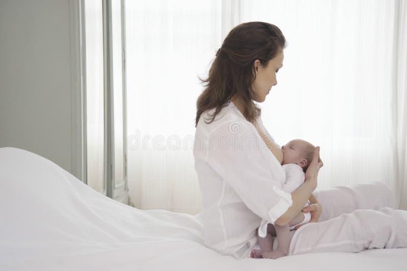 Мать кормя Newborn младенца грудью стоковые изображения rf