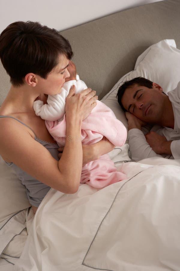 мать кровати младенца прижимаясь newborn стоковые изображения
