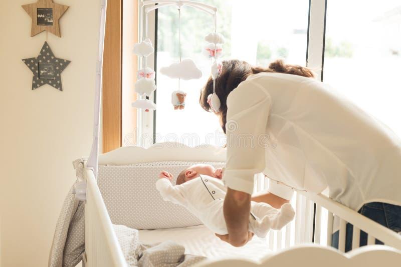 Мать кладя младенца для того чтобы спать стоковое фото rf