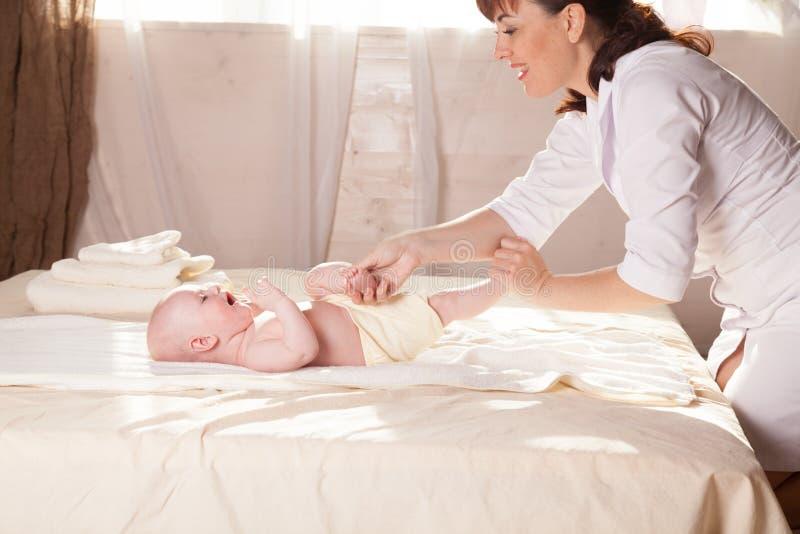 Мать младенца мальчика делая руки и ноги массажа стоковое изображение