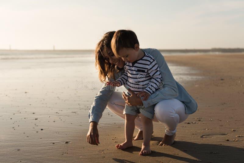 Мать на пляже с малышом стоковое фото rf