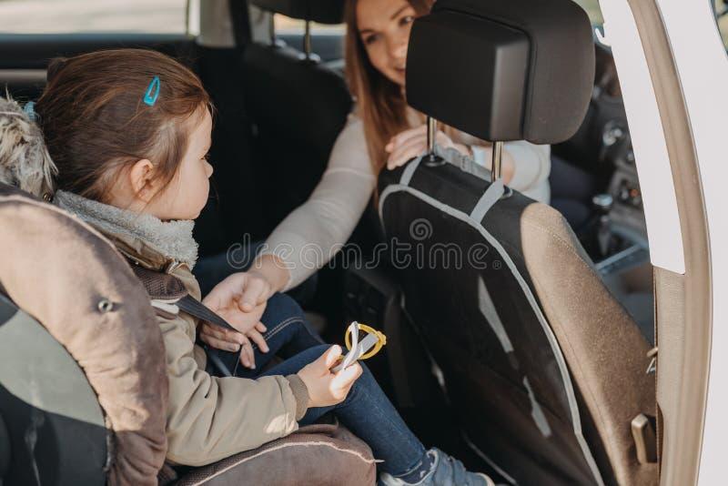 Мать обеспечивая ее дочь малыша buckled в ее место малолитражного автомобиля стоковые фотографии rf