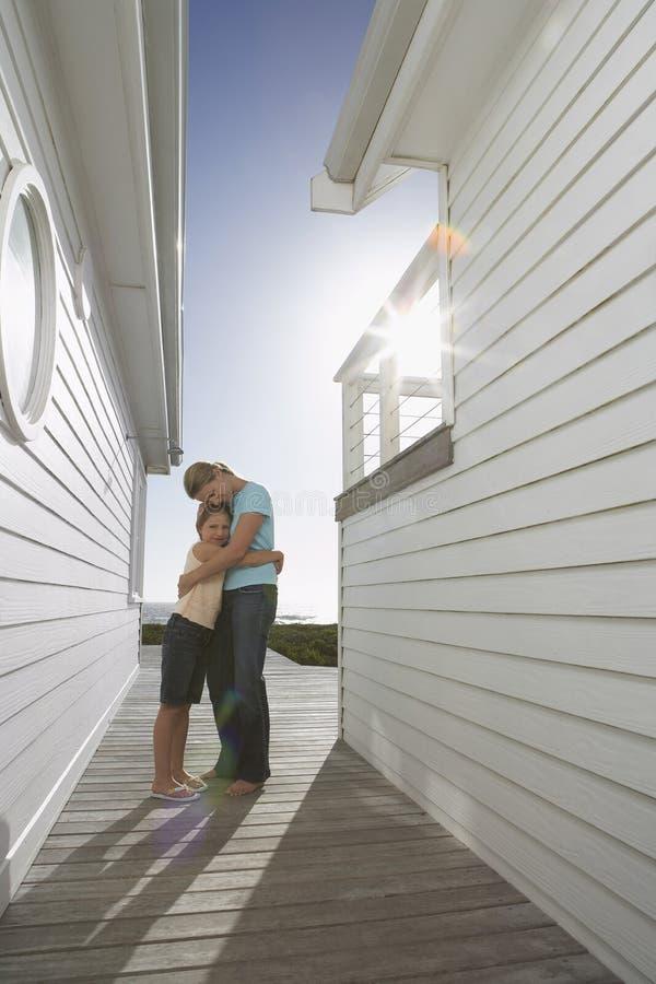 Мать обнимая дочь между пляжными домиками стоковая фотография