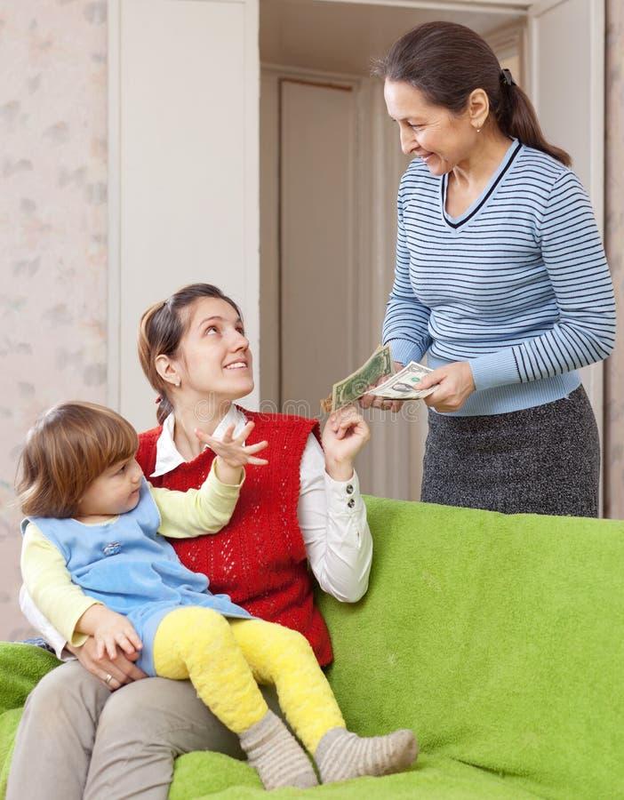 Мать оплачивает няню для ее ребенка стоковое фото rf