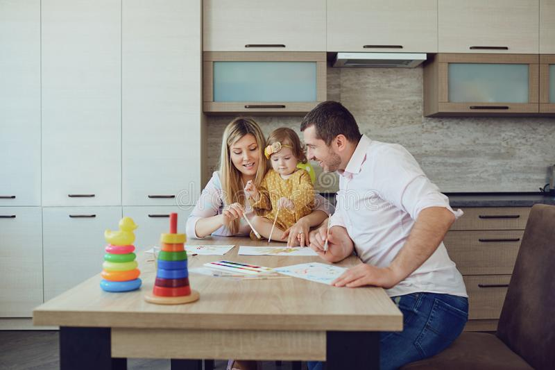 Мать, отец и ребенок рисуют совместно на таблице стоковое изображение