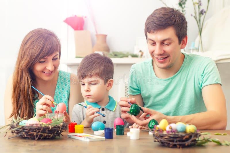 Мать, отец и сын красят яичка Счастливая семья подготавливает для пасхи стоковое изображение