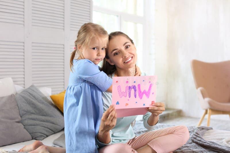 Мать получая поздравительную открытку от ее милой маленькой дочери дома стоковое изображение