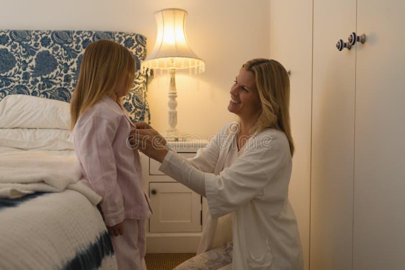 Мать помогая ее дочери в нося nightwear стоковая фотография rf