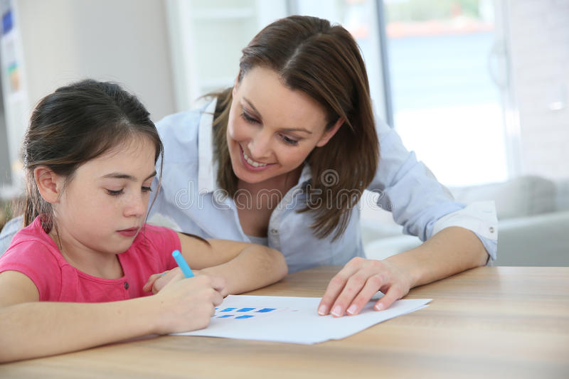 Мать помогая ее сочинительству дочери стоковые изображения rf