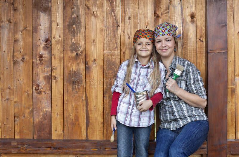 Мать порции маленькой девочки перекрашивая сарай древесины стоковое изображение