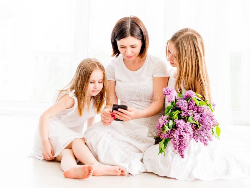 Мать при дочери смотря smartphone стоковое фото rf