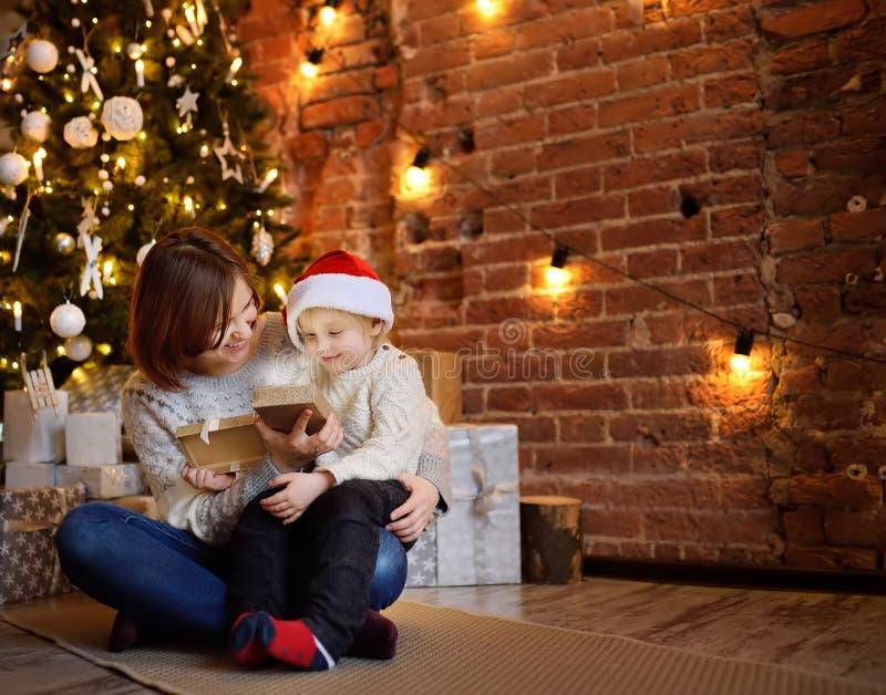 Мать при ее маленький сын раскрывая подарок рождества в уютной живущей комнате стоковая фотография