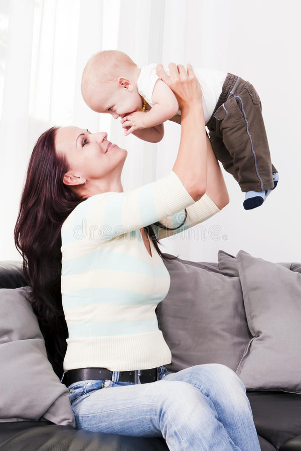 Мать при ее ребенок играя в живущей комнате. стоковые изображения rf