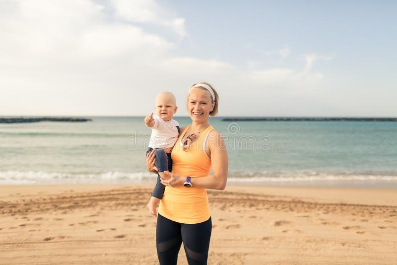 Мать при ребёнок наслаждаясь восходом солнца на пляже стоковое фото