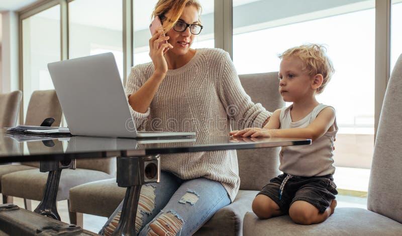 Мать при сын работая от дома стоковое фото