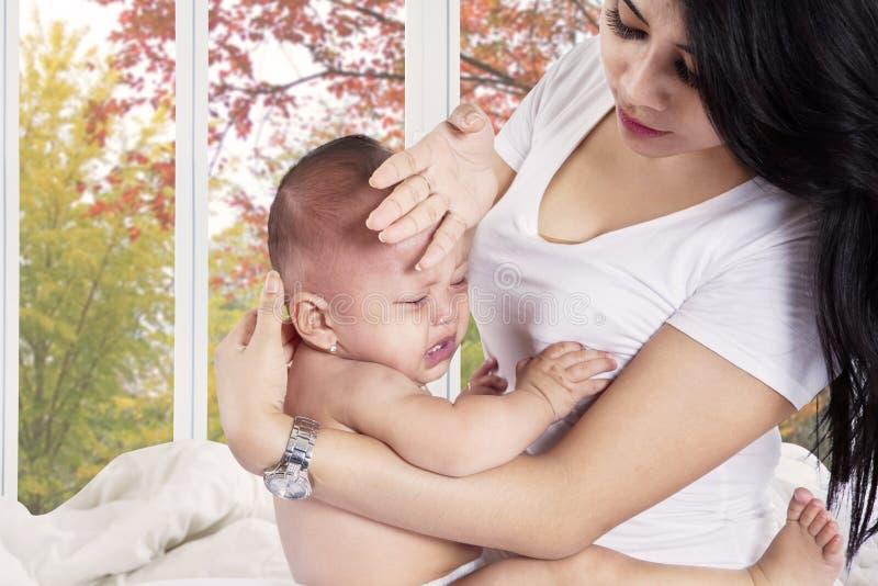 Мать проверяет температуру ее младенца стоковые изображения rf