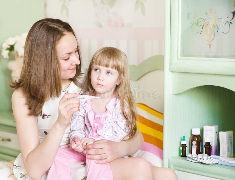 Мать проверяет температуру на больном ребенке стоковые изображения
