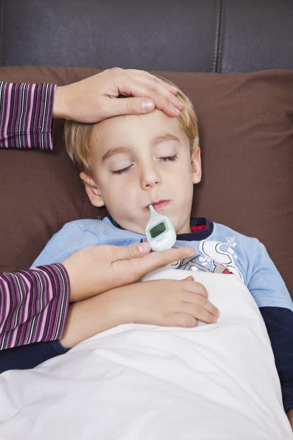 Мать проверяя нездоровую температуру мальчика с термометром стоковые изображения