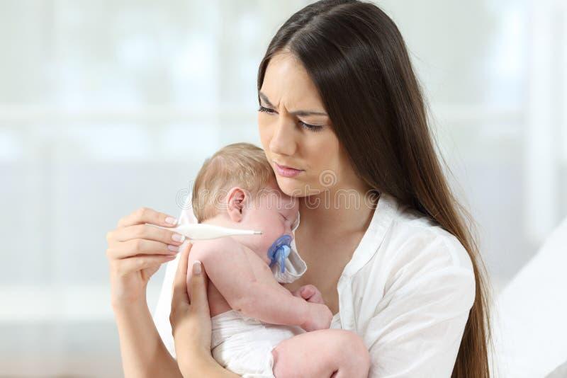 Мать проверяя термометр с больным младенцем стоковые изображения