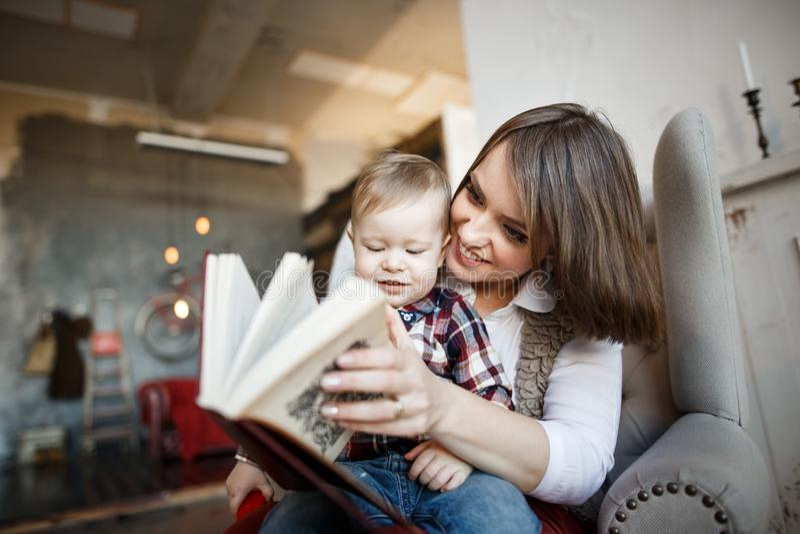 Мать сидит с ее младенцем и читает книгу Она усмехающся и смотрящ ее стоковые изображения