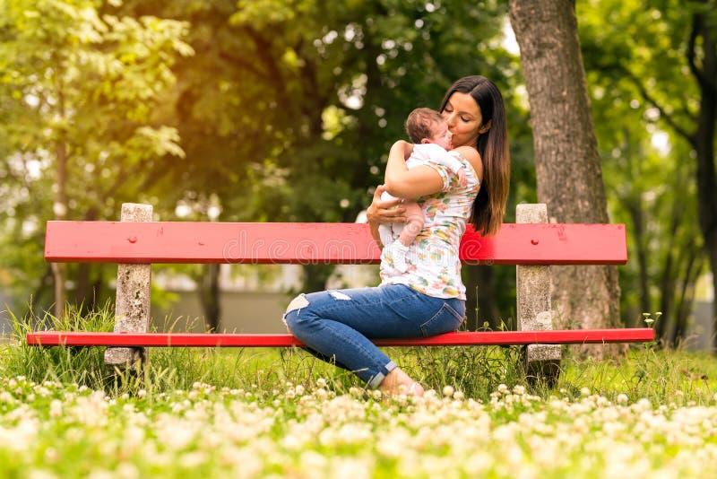 Мать сидя на стенде и держа ее младенца стоковое фото
