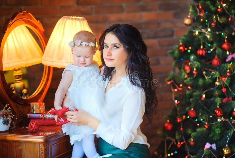 Мать сидя около зеркала держа небольшую дочь, на предпосылке праздничной рождественской елки стоковые фото